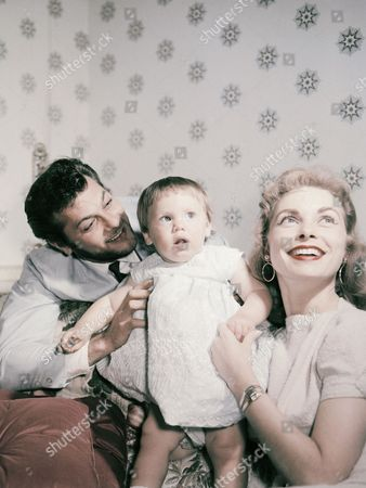 """American actor Tony Curtis, and his wife actress Janet Leigh, pose with their daughter Kelly in London, United kingdom, in June 1957, on route to Norway for the shooting of the movie """"The Vikings"""