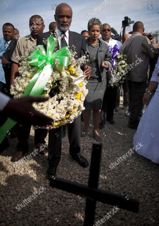 Haitian President Rene Preval, center, Haiti's first lady Elisabeth Debrosse Preval fourth from left, and Haiti Prime Minister Jean-Max Bellerive, right, carry wreaths for the victims of the Jan. 2010 earthquake during a religious ceremony at the Titanyen mass grave site on the outskirts of Port-au-Prince, Haiti, . The religious ceremony is one of many events planned to mark the one-year anniversary of the Jan. 12th magnitude-7.0 quake that killed more than 220,000 people and left millions homeless