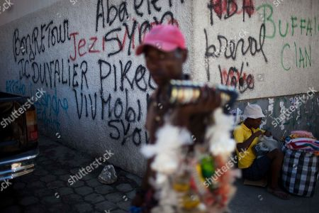 """Stock Picture of A vendor walks past graffiti that reads in French """"Welcome back J. C. Duvalier,"""" left, in downtown in Port-au-Prince, Haiti, . Haiti's former dictator Jean-Claude Duvalier returned Sunday to Haiti after nearly 25 years in exile, a move that comes as his country struggles with a political crisis and the stalled effort to recover from last year's devastating earthquake"""
