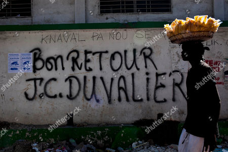 """Stock Photo of A vendor walks past graffiti that reads in French """"Welcome back J. C. Duvalier"""" in downtown in Port-au-Prince, Haiti, . Haiti's former dictator Jean-Claude Duvalier returned Sunday to Haiti after nearly 25 years in exile, a move that comes as his country struggles with a political crisis and the stalled effort to recover from last year's devastating earthquake"""