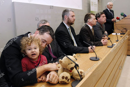 Daisy Gogarty, 18-months, left, in the arms of her father Green Party TD Paul Gogarty with other members of the Green Party, as John Gormley, Green Party leader and Environment Minister speaks during a press conference at Leinster House, Dublin, Ireland, . The junior member of the coalition, the Green Party, stunned Cowen and his Fianna Fail party by announcing Monday they want parliament dissolved in January for an early election. Ireland's banks will be pruned down, merged or sold as part of a massive EU-IMF bailout taking shape, the government said Monday as a shellshocked nation came to grips with its failure to protect and revive its banks
