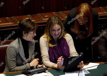 From left, Italian education minister Maria Stella Gelmini, environment minister Stefania Prestigiacomo and tourism minister Maria Vittoria Brambilla check their iPad as they attend a confidence vote at the Lower Chamber, in Rome, . Italian culture minister Sandro Bondi, a close ally of Premier Silvio Berlusconi, who came under fire weeks ago for repeated collapses inside Pompeii's 2,000-year-old archaeological site, has survived the no-confidence motion in parliament. Bondi has denied responsibility for the collapses, which proved an embarrassment for the government