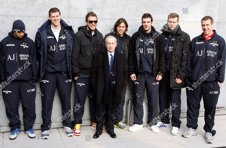 US coach Dan Peterson, center, poses with the Milan's basketball team Olimpia Milano prior to the start of Giorgio Armani men's Fall-Winter 2011/2012 collection, part of the Milan Fashion Week, unveiled in Milan, Italy
