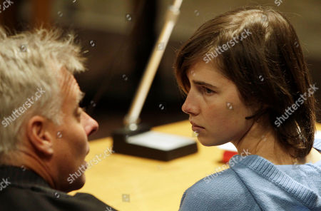 US murder suspect Amanda Knox, right, talks to her lawyer Carlo Della Vedova during a hearing in her appeals trial in the murder of her British roommate Meredith Kercher, in Perugia's courthouse, Italy, . Knox is back in court as her appeals trials opens in Italy, about a year after the American student was convicted of killing her British roommate. Wearing a blue sweater, Knox was escorted by a policewoman Wednesday into the same Perugia courtroom where the first trial was held. The 23-year-old was convicted in December of sexually assaulting and murdering Kercher, and sentenced to 26 years in prison