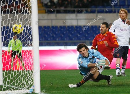 Simone Perrotta, Michael Agazzi AS Roma forward Simone Perrotta, second from right, challenged by Cagliari goalie Michael Agazzi, scores during a Serie A soccer match between AS Roma and Cagliari at Rome's Olympic stadium