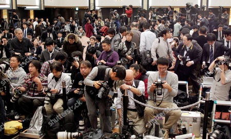 A flock of photographers and reporters prepare for a press conference by Japanese traditional Kabuki actor Ebizo Ichikawa, unseen, in Tokyo, Japan, . The Kabuki star, 33, paid a high price for a recent incident in which he sustained serious injuries to the face in a bar brawl after drinking heavily, Kyodo News reported