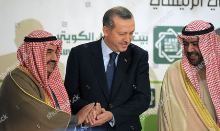 Turkish Prime Minister Recep Tayyip Erdogan, center, shakes hands with Kuwait's Prime Minister Sheikh Nasser Mohammed Al Ahmed Al Sabah, left, with Kuwait's deputy Prime Minister for Economic Affairs, Sheikh Ahmad Fahad Al Sabah, right, at the Turkish-Arab Relations Conference in Kuwait City on