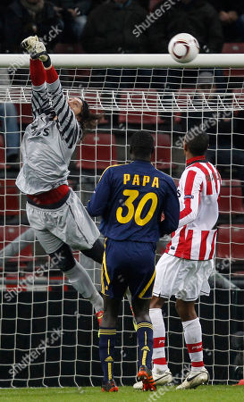 Stock Photo of PSV goalkeeper Cassio Ramos misses the ball as Metalist player Papa Gueye, center, and PSV player Marcelo look on during the Europa League group I soccer match at Philips stadium in Eindhoven, Netherlands, . The match ended in a 0-0 draw