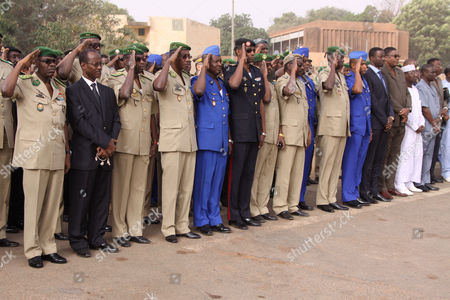 Stock Photo of Government officials and military officers, including Salou Djibo, left, leader of the ruling military junta, pay homage to three Nigerien soldiers killed during a weekend attempt to rescue two french hostages, in Niamey, Niger . Paris anti-terrorism investigators have gone to Niger to probe the deaths of two French hostages killed amid a rescue operation led by French special forces, a judicial official said Monday