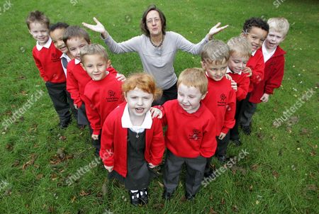 """Pictured is Reception Class teacher and Acting Deputy Head Lynda Pollard with  twin pupils L-R : Harry Parker, Starla Tyler, Joshua Longhurst, Lewis Kilby, Chloe Pryke, Matthew Pryke,  Owen Kilby, Jacob Longhurst, Tyler Banks and Max Parker. Teachers are seeing double at a primary school where no less than 5 sets of twins have joined the reception class. The twins are all in their first week at Ramsey Spinning Infant School, near Huntingdon, Cambridgeshire, and will count for almost one in seven pupils in their year. Patsy Barrett, acting headteacher, said: """"It's fantastic we've got them and it's going to be interesting watching them develop."""""""