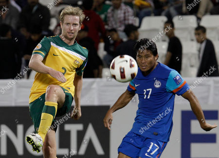 Australia's David Carney, left, kicks the ball India's Surkumar Singh, right, looks at him during their AFC Asian Cup group C soccer match at Al-Sadd Stadium, in Doha, Qatar