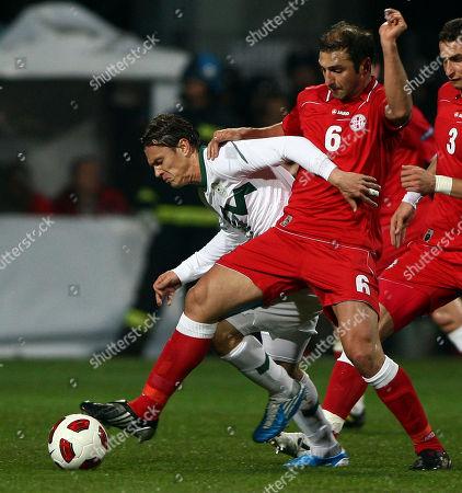 Georgia's Zurab Khizanishvili, right, is challenged by Slovenia's Zlatko Dedic during a friendly soccer match between Slovenia and Georgia in Koper, Slovenia, Wednsday, Nov. 17, 2010