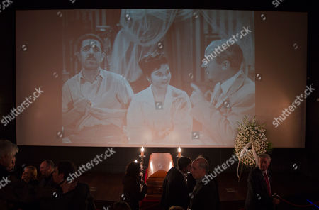 Stock Photo of Well wishers pass by the coffin of Spanish film director Luis Garcia Berlanga, at the Spanish Film Academy in Madrid . Spanish cinema is in mourning for one of its leading lights. Berlanga had been suffering from Alzheimer's disease and is survived by a son, Fernando. A projection of one of his movies is seen in the background