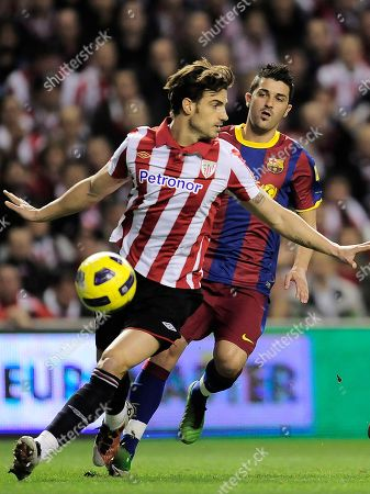 David Villa, Aitor Ocio Barcelona's David Villa, background, looks on as Athletic Bilbao's Aitor Ocio protects the ball during their Spanish second-leg Copa del Rey soccer match at San Mames stadium in Bilbao northern Spain Wednesday Jan.5, 2011