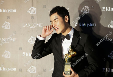 """Ethan Juan Best Leading Actor Taiwanese actor Ethan Juan wipes tears as he holds his award for film """"MONGA"""" at the 47th Golden Horse Awards, in Taoyuan County, northern Taiwan. The Golden Horse Awards is the Chinese-language film industry's biggest annual events"""
