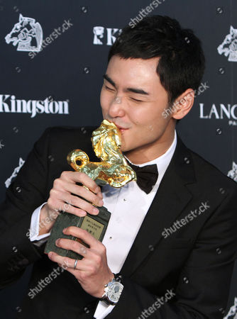 """Taiwanese actor Ethan Juan kisses his award for Best Leading Actor for the film """"MONGA"""" at the 47th Golden Horse Awards, in Taoyuan County, northern Taiwan. The Golden Horse awards are the Chinese-language film industry's biggest annual events"""