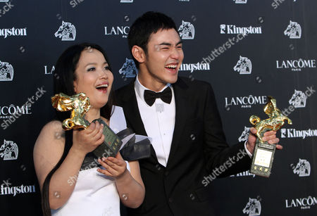 """Best Leading Actor Taiwanese actor Ethan Juan, right, and Chinese actress Lv Li-Ping hold their awards after their film """"MONGA"""" and """"City Monkey"""" at the 47th Golden Horse Awards, in Taoyuan County, northern Taiwan. The Golden Horse Awards is the Chinese-language film industry's biggest annual events"""