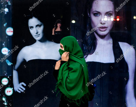 Stock Picture of An Afghan woman walks past posters of Hollywood actor Anjelina Jolie, right, and Bollywood actor Katrina Kaif, left, at a street in Kabul, Afghanistan