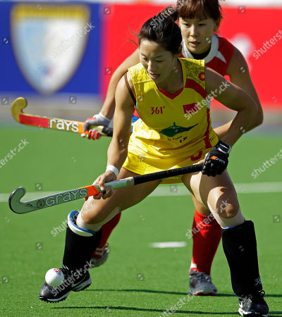 China's Li Shuang, front, fights for the ball with South Korea's Kim Da Rae during a Women's Hockey World Cup match in Rosario, Argentina, . South Korea won 2-1