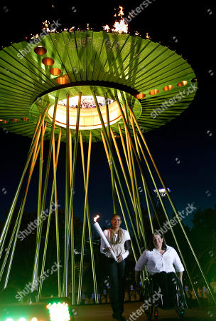 Cathy Freeman, Louise Savage Olympic gold medalist Cathy Freeman, left, and Paralympic gold medalist Louise Savage re-enact lighting the cauldron in Sydney, Australia, during the city's 10th anniversary celebrations of the Olympics