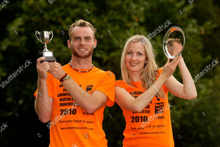 Garret Doherty of the Republic of Ireland, left, and Manchester runner Rachel Butterfield pose with their trophies after winning the first UK Backward Running Championships at Heaton Park, Manchester, England, . 35 entrants competed over a one mile circuit won by Doherty in a time of 6 minutes and 30 seconds and Butterfield, the fastest woman, in a time of 12 minutes and 40 seconds