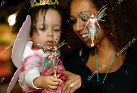 Stock Picture of Danielle Brown, Mimi Brown Sister of British singer Mel B, Danielle Brown and her daughter Mimi poes with two Flitter Fairies on sale at Hamleys toy shop in London, . Hamleys reveal Tuesday the Flitter Fairies is to be a best seller girl's toy this Christmas