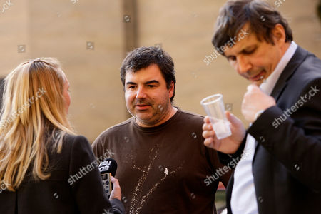 Dr Konstantin Novoselov, centre, and Professor Andre Geim, right, who have have been awarded the Nobel Prize for Physics are interviewed outside Manchester University, Manchester, England, . The scientists won the prize for their work on Graphene, the world's thinnest material. It has rapidly become one of the hottest topics in materials science and solid-state physics
