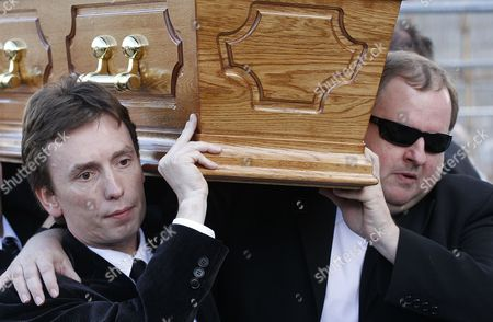 Snooker player Ken Doherty, left, carries the coffin of former world snooker champion Alex Higgins from the family home in South Belfast, Northern Ireland