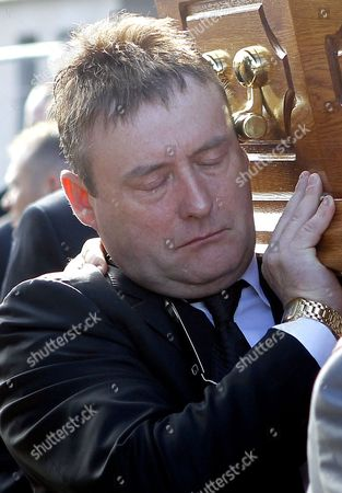 Snooker player Jimmy White, left, carries the coffin of former world snooker champion Alex Higgins from the family home in South Belfast, Northern Ireland