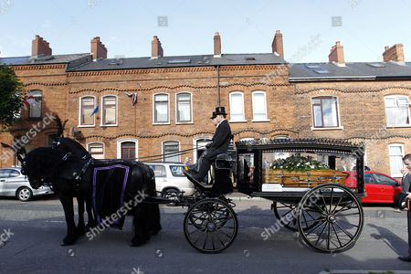 A horse drawn hearse carries the Coffin of former world snooker champion Alex Higgins from the family home in South Belfast, Northern Ireland