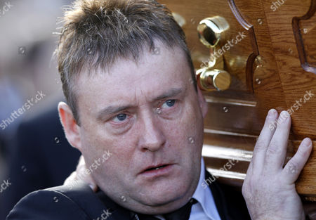 Snooker player Jimmy White carries the coffin of former world snooker champion Alex Higgins from the family home in South Belfast, Northern Ireland