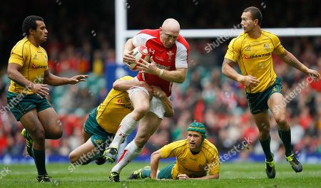 Wales' Tom Shanklin runs with the ball as he is tackled by Australia's Benn Robinson, during their international rugby union match at Cardiff's Millennium stadium in Cardiff, Wales