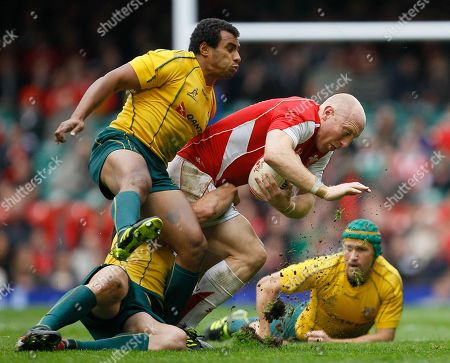 Wales' Tom Shanklin runs with the ball as he is tackled by Australia's Benn Robinson, hidden and Will Genia left during their international rugby union match at Cardiff's Millennium stadium in Cardiff, Wales