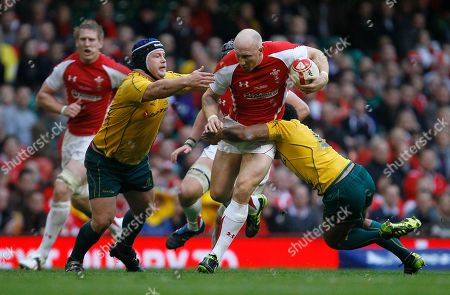 Wales' Tom Shanklin runs with the ball as he is tackled by Australia's Benn Robinson, left, and Will Genia during their international rugby union match at Cardiff's Millennium stadium in Cardiff, Wales