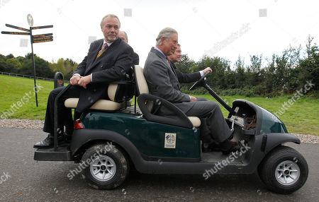Britain's Prince Charles, right, and Sir Terry Matthews, left, owner of the Celtic Manor Resort where the 2010 Ryder Cup golf tournament is to take place, rides in a golf buggy through the resort in Newport, Wales, . Men at right unidentified