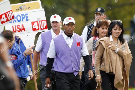 Tiger Woods, front center, and teammate Steve Stricker, center rear, walks with Lisa Pavin, right, wife of U.S. team captain Corey Pavin, on the second day of the 2010 Ryder Cup golf tournament at the Celtic Manor Resort in Newport, Wales