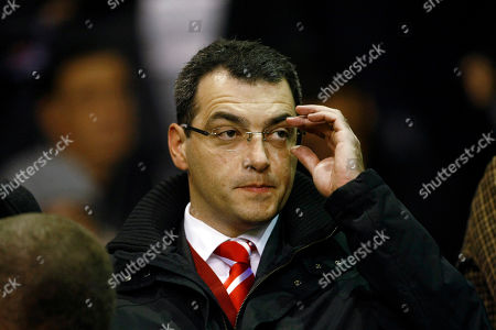 Liverpool's new director of football strategy Damien Comolli takes his seat before the team's Europa League soccer match against Napoli at Anfield Stadium, Liverpool, England