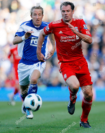 Liverpool's Jamie Carragher, right, vies for the ball with Birmingham's Lee Bowyer during their English Premier League soccer match at Birmingham's St Andrew's Stadium in Birmingham, . (AP Photo/Kirsty Wigglesworth) ** NO INTERNET/MOBILE USAGE WITHOUT FOOTBALL ASSOCIATION PREMIER LEAGUE(FAPL)LICENCE. CALL +44