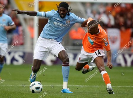 Manchester City's Emmanuel Adebayor, left, vies for the ball with Blackpool's Elliot Grandin, right, during their English Premier League soccer match at Bloomfield Road, Blackpool, England, . (AP Photo/Scott Heppell) ** NO INTERNET/MOBILE USAGE WITHOUT FOOTBALL ASSOCIATION PREMIER LEAGUE(FAPL)LICENCE. CALL +44