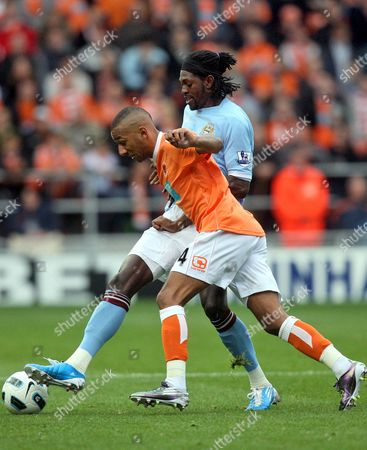 Manchester City's Emmanuel Adebayor, right, vies for the ball with Blackpool's Elliot Grandin, left, during their English Premier League soccer match at Bloomfield Road, Blackpool, England, . (AP Photo/Scott Heppell) ** NO INTERNET/MOBILE USAGE WITHOUT FOOTBALL ASSOCIATION PREMIER LEAGUE(FAPL)LICENCE. CALL +44