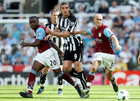 Aston Villa's Stephen Ireland, right, Nigel Reo-Coker, left, vie for the ball with Newcastle United's Andy Carroll, center, during their English Premier League soccer match at St James' Park, Newcastle, England, . (AP Photo/Scott Heppell) ** NO INTERNET/MOBILE USAGE WITHOUT FOOTBALL ASSOCIATION PREMIER LEAGUE(FAPL)LICENCE. CALL +44