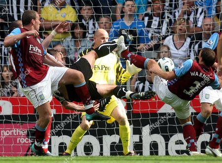 Newcastle United's captain Kevin Nolan, center, scores past Aston Villa's Richard Dunne, left, goalkeeper Brad Friedel, center, and Stephen Warnock, right, during their English Premier League soccer match at St James' Park, Newcastle, England, . (AP Photo/Scott Heppell) ** NO INTERNET/MOBILE USAGE WITHOUT FOOTBALL ASSOCIATION PREMIER LEAGUE(FAPL)LICENCE. CALL +44