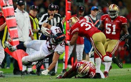 Denver Broncos' Dan Gronkowski, left, is tackled by San Francisco 49ers' Will James, right, and San Francisco 49ers' Nate Clements, center, during the NFL Football match between the Denver Broncos and San Francisco 49ers at Wembley Stadium in London