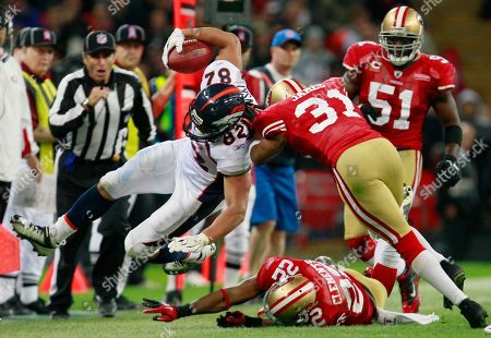 Denver Broncos' Dan Gronkowski, left, is tackled by San Francisco 49ers' Nate Clements, center, and San Francisco 49ers' Will James, second from right, during the NFL Football match between the Denver Broncos and San Francisco 49ers at Wembley Stadium in London
