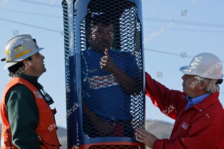 Alberto Segovia, brother of trapped miner Dario Segovia, gives a thumbs up as he stands in the capsule that will be used to rescue trapped miners from the collapsed San Jose mine as Rescue Operation Deputy Rene Aguilar, left, and Health Minister Jaime Manalich look on in Copiapo, Chile, . Thirty-three miners have been trapped deep underground in the copper and gold mine since it collapsed on Aug. 5