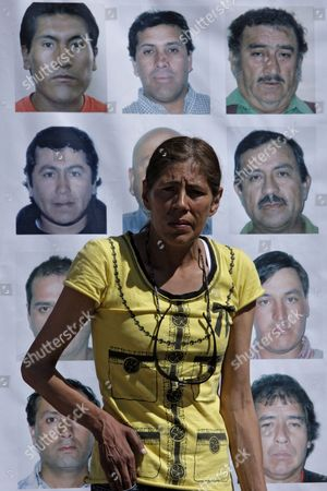 Maria Angelica Munoz, partner of Jose Ojeda, one out of 33 miners trapped at the San Jose mine in Copiapo, Chile, walks past a banner with pictures of the trapped miners outside the mine, . The miners have been trapped deep underground in the copper and gold mine since it collapsed on Aug. 5