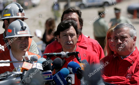 Chile's Mining Minister Laurence Golborne talks to journalists at the San Jose Mine near Copiapo, Chile, . Authorities said all would be in place at midnight Tuesday to begin the rescue of the 33 trapped miners. At right is Chile's Health Minister Jaime Manalich
