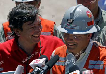 Andres Sougarret, center, the chief engineer in charge of the rescue mission of 33 trapped miners, right, and Chile's Mining Minister Laurence Golborne smiles during a joint press conference at the San Jose Mine near Copiapo, Chile, . Sougarret, a 46-year-old mining engineer, was in charge of digging the miners out