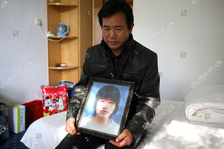 """Chen Guangqian On, Chen Guangqian holds a portrait of his daughter Chen Xiaofeng at a hotel room in Baoding in northern China's Hebei province. Chen's daughter was killed in a hit-and-run that has become the country's hottest crime in months because of what the driver reportedly shouted when a crowd stopped his car. """"My father is Li Gang!"""", the deputy chief of the district police"""