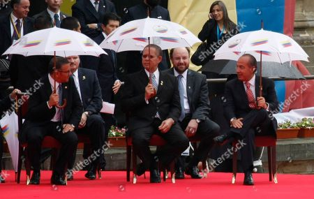 Stock Photo of Mauricio Funes, Orette Bruce Golding, Felipe Calderon El Salvador's President Mauricio Funes, left, speaks with his Mexican counterpart President Felipe Calderon, right, while Jamaica's Prime Minister Orette Bruce Golding looks on during the swearing-in ceremony of Colombia's President Juan Manuel Santos in Bogota, Colombia